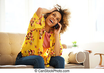 beautiful african american girl smiling at home while talking on mobile phone