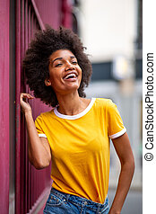 beautiful african american woman laughing outside in city