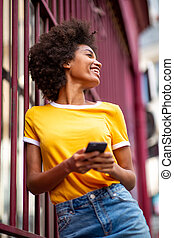 beautiful african american woman laughing with cellphone