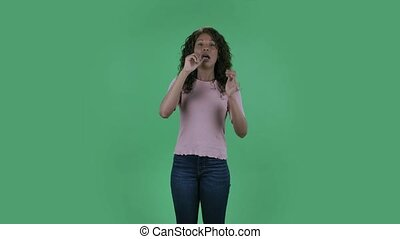 Portrait of beautiful african american young sick woman is looking at camera . She has temperature and cough. Burning brunette with wavy hair in jeans and a beige blouse on a green screen in the studio. Health Protection Corona Virus Concept
