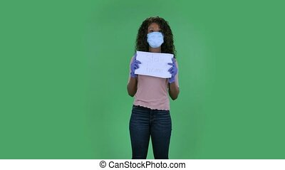 Portrait of beautiful african american young woman in medical mask is looking at camera and holding a poster with the words stay home. Burning brunette with wavy hair in jeans and a beige blouse on a green screen in the studio. Health Protection Corona Virus Concept