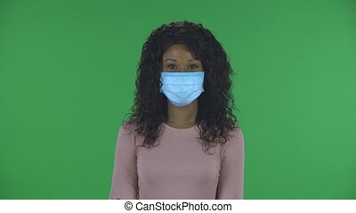 Portrait of beautiful african american young woman in medical mask is looking straight and talking to someone. Burning brunette with wavy hair in jeans and a beige blouse on a green screen in the studio. Health Protection Corona Virus Concept.