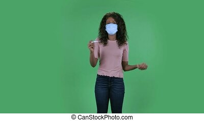 Portrait of beautiful african american young woman in medical protective face mask is looking at camera and holding a thermometer. She has fever waves her hand to cool herself. Burning brunette with wavy hair in jeans and a beige blouse on a green screen in the studio. Health Protection Corona Virus...
