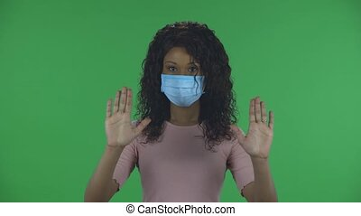 Portrait of beautiful african american young woman in medical protective face mask looking at camera and strictly gesticulates with hands crossed making X shape meaning denial saying NO and STOP. Burning brunette with wavy hair in jeans and a beige blouse on a green screen in the studio. Health ...