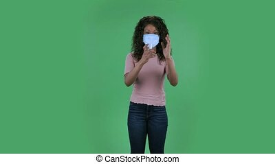 Portrait of beautiful african american young woman in medical protective face mask looking at camera and applying antiseptic on her hands in order to prevent the spread of coronavirus. Burning brunette with wavy hair in jeans and a beige blouse on a green screen in the studio. Health Protection Corona Virus Concept.