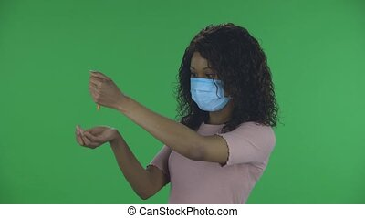 Portrait of beautiful african american young woman in medical protective face mask pours medicine from hand to hand in order to prevent the spread of coronavirus. Burning brunette with wavy hair in jeans and a beige blouse on a green screen in the studio. Health Protection Corona Virus Concept.