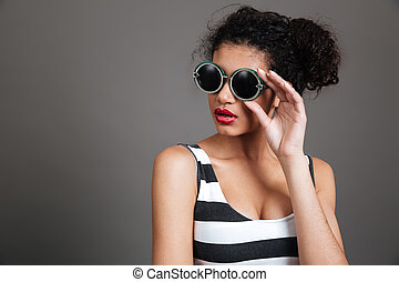 Portrait of beautiful african american young woman in round glasses