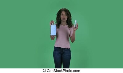 Portrait of beautiful african american young woman is looking straight and holding in hands a medical mask and an antiseptic. Burning brunette with wavy hair in jeans and a beige blouse on a green screen in the studio. Health Protection Corona Virus Concept