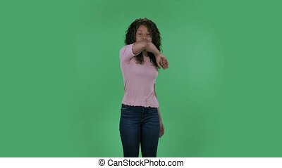 Portrait of beautiful african american young woman is looking straight . She has temperature is coughs and covers itself with an elbow. Burning brunette with wavy hair in jeans and a beige blouse on a green screen in the studio. Health Protection Corona Virus Concept