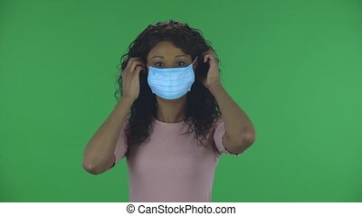 Portrait of beautiful african american young woman puts on medical mask. Burning brunette with wavy hair in jeans and a beige blouse on a green screen in the studio. Health Protection Corona Virus Concept