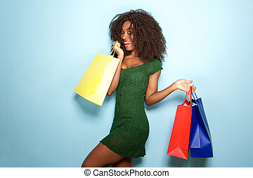 beautiful african girl happy with shopping bags on blue background