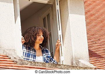 African teenage girl in country house attic window