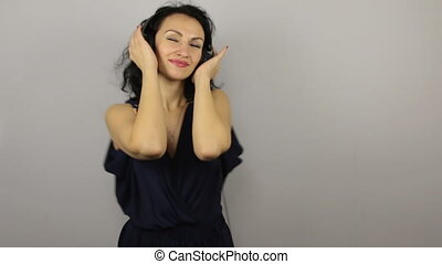 Portrait of beautiful and sexy woman dancing in headphones