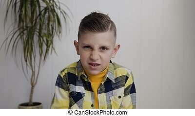 Portrait of beautiful angered 7- 8 years boy who sits on the floor over white wall background. Boy making angry face and shows a fist at the camera