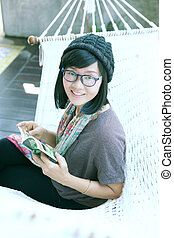 portrait of beautiful asian woman relaxing time reading book on cradle happiness emoton with smiling face