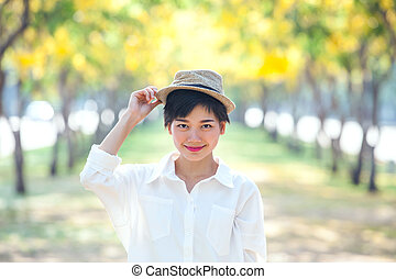 portrait of beautiful asian woman standing in blooming flowers park with happiness emotion