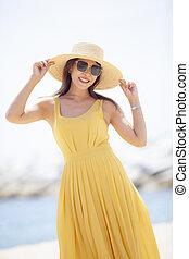 portrait of beautiful asian younger woman wearing yellow dress standing on sea beach