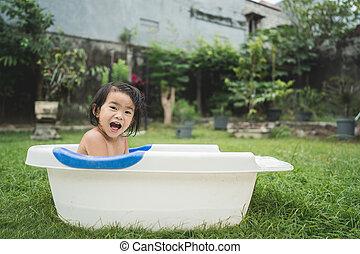 beautiful baby girl take a bath in a baby bath tube