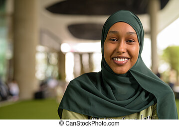 Portrait of beautiful black African Muslim woman smiling outdoors