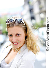 Portrait of beautiful blond girl in town