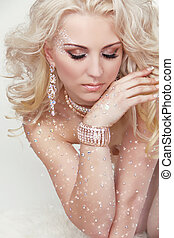 Portrait of beautiful blond girl with long curly hair and professional make-up. Jewelry. Beauty. Fashion woman.