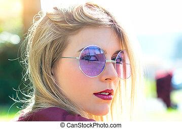 Portrait of beautiful blond girl with transparent purple eyeglasses