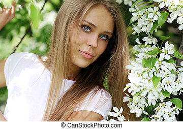 Portrait of beautiful blond in spring blossom
