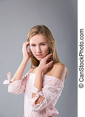 portrait of beautiful blond smillingl woman in pink cocktail dress on grey background