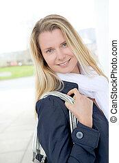 Portrait of beautiful blond woman in town