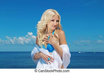 Portrait of beautiful blond woman on blue sky background