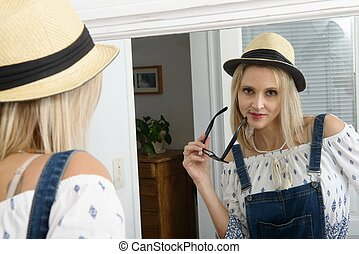 beautiful blond woman posing with summer hat in the mirror