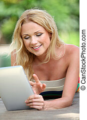Portrait of beautiful blond woman using electronic tablet