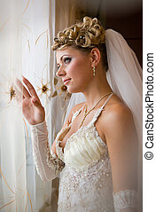 Portrait of beautiful blonde bride with makeup wearing in Classic White