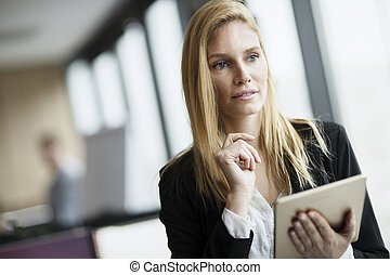 Portrait of beautiful blonde businesswoman holding tablet