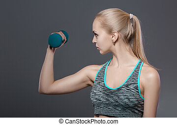 portrait of beautiful blonde girl in sportswear does exercises with dumbbells on dark background