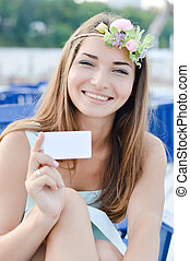 portrait of beautiful blonde girl young woman having fun happy smiling with flowers in her head holding blank copy space business card & looking at camera on summer or spring outdoors background image