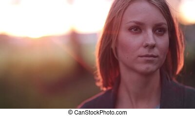 Portrait of beautiful blonde pensive woman outdoor in the summer, looking into the distance on sunset, close-up
