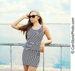 Portrait of beautiful blonde woman in sunglasses and striped dress over sea