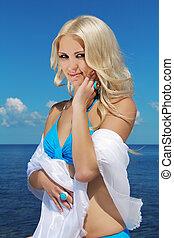 Portrait of beautiful blonde woman on blue sky background
