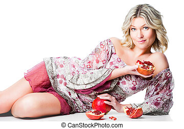Portrait of beautiful blonde woman with two pomegranates lying on isolated white background