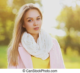 Portrait of beautiful blonde young woman looking at camera outdoors