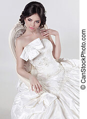 Portrait of beautiful bride in magnificent wedding dress sitting on luxury chair. Girl model. Studio.