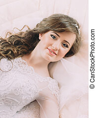 Portrait of beautiful bride in white dress and veil on bed in wedding day