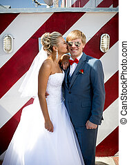 beautiful bride kissing handsome groom in sunglasses on street