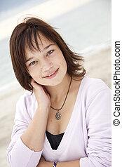 Portrait of beautiful brunet girl on the beach.