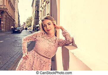 Portrait of beautiful brunette model in the city street during a sunny day, looking at the camera. Vintage toning effect