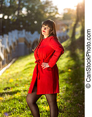 beautiful brunette woman in red coat posing at autumn forest