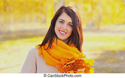 Portrait of beautiful brunette woman wearing scarf with yellow maple leaves in autumn park