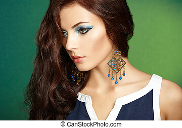 Portrait of beautiful brunette woman with earring. Perfect makeup. Fashion photo