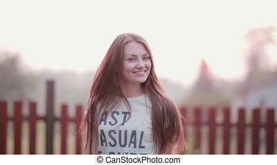 Portrait of beautiful brunette young woman smiling outdoor, turns and looking at camera cheerful on sunset